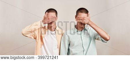 Two Caucasian Men, Twin Brothers Covering Eyes With Hand While Posing Together Isolated Over Beige B