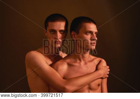 Portrait Of Young Half Naked Twin Brothers Posing Together In Studio, Standing Isolated Over Brown B