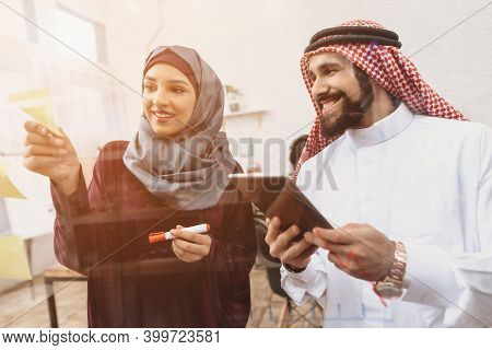 Arab Man And Woman Working In Offce. Coworkers Are Writing Notes On Glass Board.