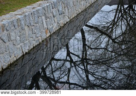 The Stone-clad Retaining Walls Of The River Pond Reservoir Or Dock Are Inaccessible To Humans. The A