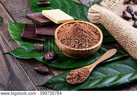 Cocoa Powder In Wooden Bowl, Bars Of Dark Bitter Chocolate And Cocoa Butter With Whole Dry Cacao Bea