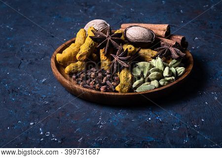 Dry Warming Indian Spicesin On Plate For Autumn Winter Meal On Dark Blue Concrete Background. Exotic