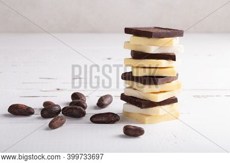 Stack Of Raw Dark Bitter Chocolate And Cocoa Butter With Cocoa Beans On Old Rustic White Table With