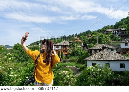 Hipster With Hat Taking A Selfie Smiling For Social Media And Old Town With Abandon House On Backgro