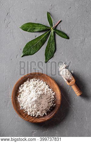 Cassava (manioc) Flour In Wooden Bowl With Original Leaf On Grey Background Top View. Alternative Gl