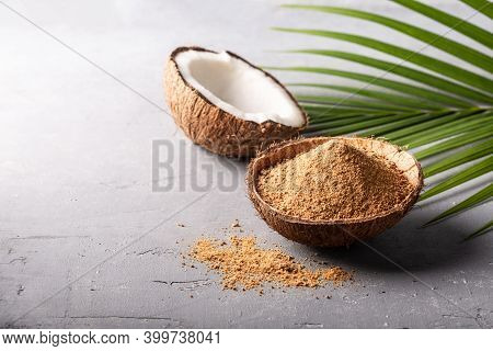 Organic Brown Palm Or Coconut Sugar In Coconut Bowl With Palm Leaf On Grey Concrete Background Copys