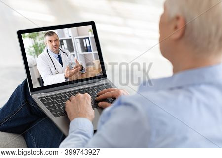 Elderly Woman Using Laptop At Home, Making Video Call With Doctor, Having Online Conference With Med