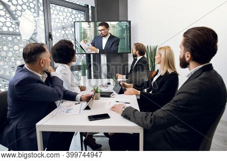 Team Of Five Focused Multiethnical Businesspeople Looking At Screen, Having Video Conference In Mode