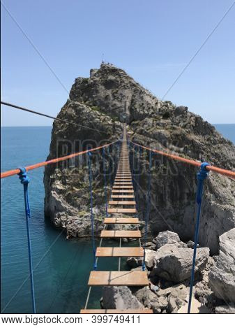 Dangerous Wooden Bridge Hanging Over The Water In Summer. Risky Hiking Adventure To Beautiful Travel