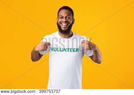 Volunteers Portrait. Happy Black Activist Man Showing His T-shirt With Volunteer Print Inscription O