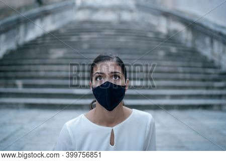 Fearful Woman Looking Shocked/sceptic Wearing A Face Mask In Empty Streets.pandemic Future Concept.n