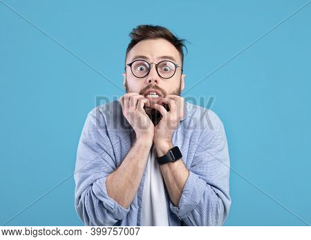 Scared Millennial Guy Biting Nails In Panic Over Blue Studio Background. Horrified Young Man Feeling