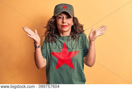 Middle age brunette woman wearing t-shirt and cap with red star symbol of communism clueless and confused with open arms, no idea and doubtful face.