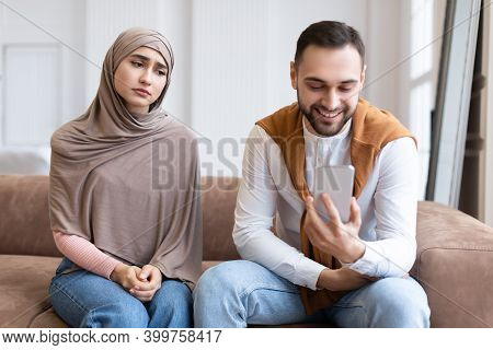 Infidelity. Unhappy Muslim Wife Looking At Cheating Husband While He Texting On Phone With Other Wom