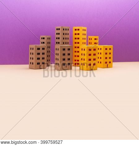 Miniature City With Yellow Brown Houses On Purple Beige Background. Abstract Urban Architecture Land