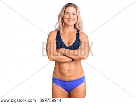 Middle age fit blonde woman wearing bikini happy face smiling with crossed arms looking at the camera. positive person.