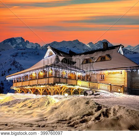 Wooden Cottage Against Peaks Of Mountains During Christmas Time