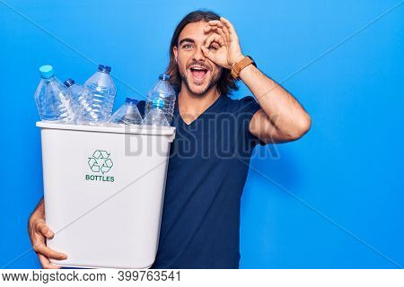 Young handsome man holding recycling wastebasket with plastic bottles smiling happy doing ok sign with hand on eye looking through fingers