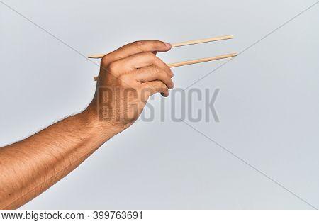 Hand of hispanic man holding wooden chopsticks over isolated white background.