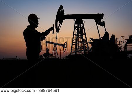 Silhouette Of A Chemical Engineer Taking A Sample Of Crude Oil Against The Background Of Oil Pumps.