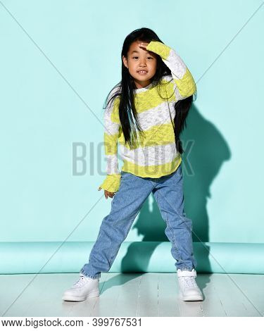 Stylish Little Asian Woman Presses Her Hand To Her Forehead And Looks Into The Distance. A Child In