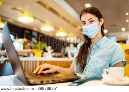Young Woman In A Public Place Working On Laptop, Wearing Protective Face Mask Indoors.online Trainin