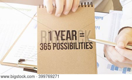 Text 1 Year 365 Possibilities On Brown Paper Notepad In Businessman Hands On The Table With Diagram.
