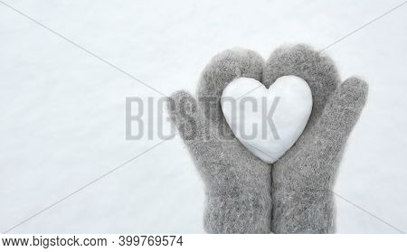 Women's Hands In Light Gray Knitted Mittens Hold A Beautiful White Heart Made Of Snow, Copy Space