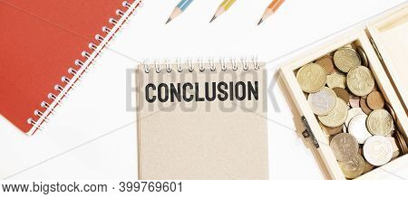 Calculator, Red Notepad, Three Colour Pencils, Silver Pen And Brown Notebook With Text Conclusion