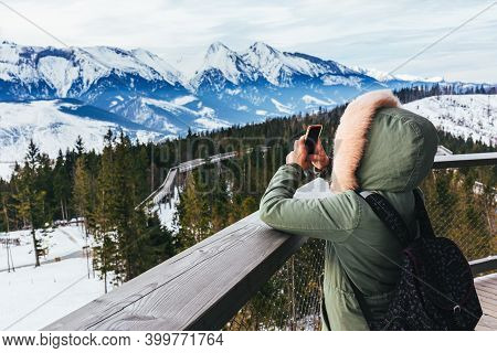 Girk Taking Pictures Of Mountain Landscape On Camera Phone. Winter Mountain Landscape In High Tatry,