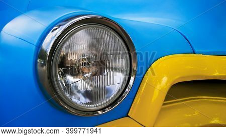 Headlight Of A Blue Vintage Car On The Background Of A Yellow Car