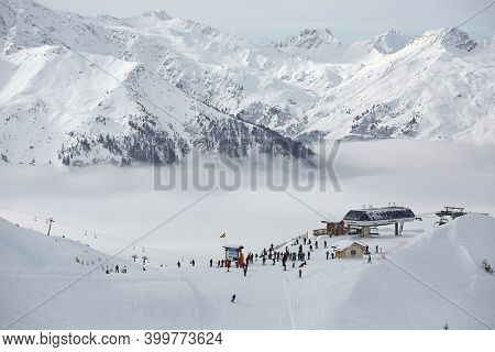 Les Arcs, Paradiski, France - Circa 2016: Skiing slopes in the French Alpes above the clouds, winter ski resort high mountain snowy landscape. People using ski lifts.
