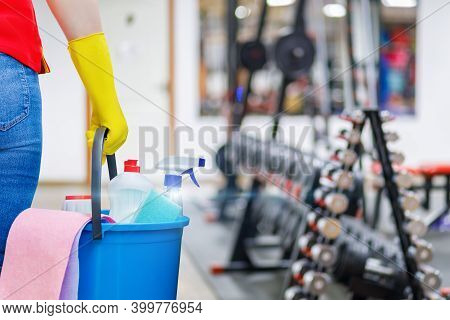 Gym Cleaning Concept. Cleaning Lady Stands With A Bucket And Cleaning Products On The Background Of