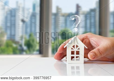 Real Estate Questions Answers Concept. Hand Shows A House With A Question Mark On A Blurred Backgrou