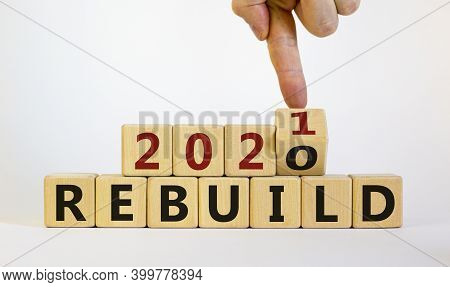 Symbol Of 2021 Rebuild. Male Hand Flips Wooden Cubes And Changes The Inscription 'rebuild 2020' To '