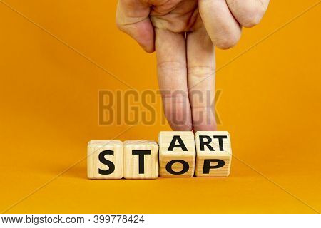 Business And Stop Or Start Concept.male Hand Flips A Wooden Cube And Changes The Word 'stop' To 'sta