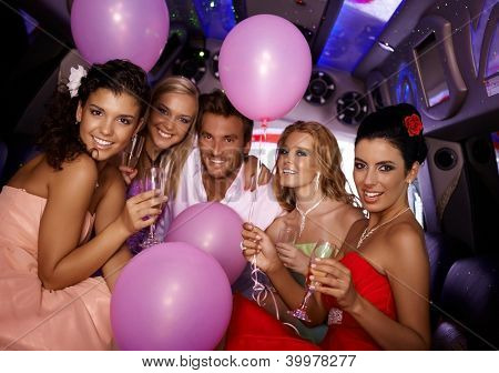 Attractive young people having party in limousine.