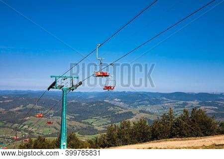 Empty Mountain Ski Chairlift In Summer. Forest Mountains Panorama On The Horizon. Travel Concept.