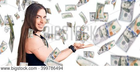Young adult man with long hair wearing goth style with black clothes pointing aside with hands open palms showing copy space, presenting advertisement smiling excited happy