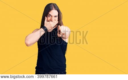 Young adult man with long hair wearing goth style with black clothes laughing at you, pointing finger to the camera with hand over mouth, shame expression
