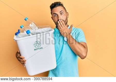 Handsome man with beard holding recycling wastebasket with plastic bottles covering mouth with hand, shocked and afraid for mistake. surprised expression
