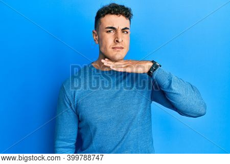 Hispanic young man wearing casual winter sweater cutting throat with hand as knife, threaten aggression with furious violence