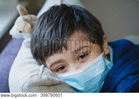 Close Up Face Of Sick Child Wearing A Protective Mask, Ill Child In Medical Face Mask Lying Head On