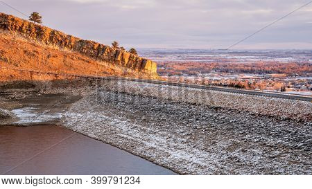 sunrise light over Horsetooth Reservoir, dam and city of Fort Collins - winter scenery with a low water level