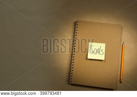 Brown Notebook With Yellow Sticky Note Top View For Goal Or To Do List Notepad, Brown Background Tex