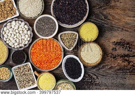 Food Background Of Various Cereals And Grains In Plates On A Wooden Table