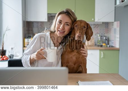 Woman In Sleepwear Hugging Her Beloved Wirehaired Vizsla Dog, Sitting On The Chair In Kitchen Room I
