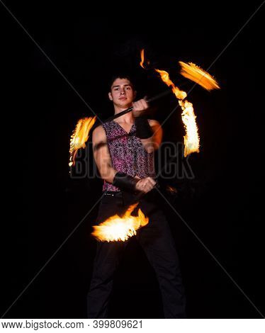 Burning Energy. Handsome Man Juggle Flaming Batons. Fire Juggling. Fire Energy. Energetic Twirling.