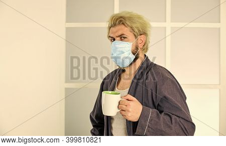Man Drinks Coffee In Medical Mask. Morning At Home On Coronavirus Self Isolation. Pandemic Quarantin