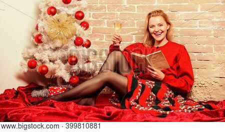 Girl In Red Dress Relaxing With Glass Of Champagne Near Christmas Tree. Waiting For Christmas. Woman